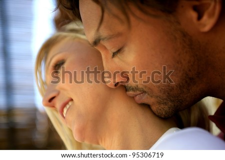 Man kissing his girlfriend's neck