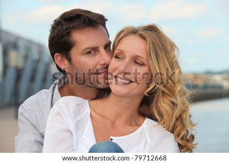 Man kissing his partner by the water