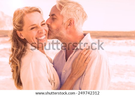 Photo of Man kissing his smiling partner on the cheek at the beach on a sunny day