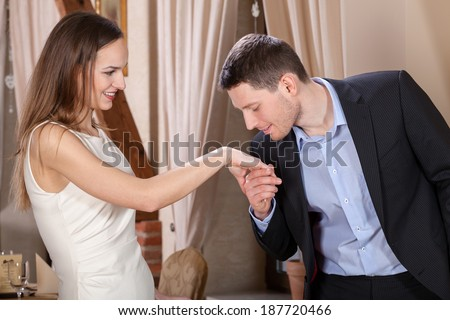 Man kissing his wife\'s hand before dinner