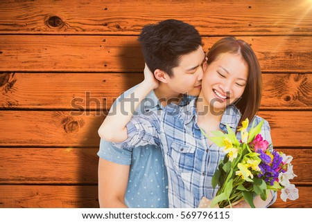 Man kissing woman with bouquet against red paint splashed surface #569796115