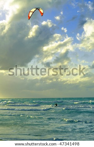 Man kite-surfing in Atlantic Ocean in dramatic weather and lighting - stock photo