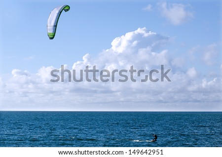 Man Kite surfing or Kite boarding, adventure surface water sport, combination of the wake boarding, windsurfing, surfing, paragliding, and gymnastics into one extreme sport