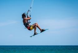 man kitesurfer athlete jumping while performing kite-surfing jump kite-boarding school kite spot