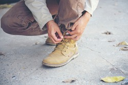 Man kneel down and tie shoes industry boots for worker. Close up shot of man hands tied shoestring for his construction brown boots.  Close up man hands tie up shoes for footwear concept.