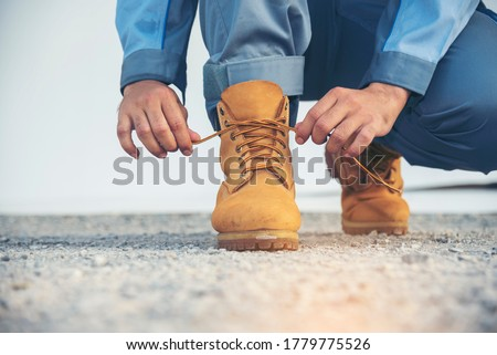 Man kneel down and tie shoes industry boots for worker. Close up shot of man hands tied shoestring for his construction brown boots.  Close up man hands tie up shoes for footwear concept. Foto stock ©