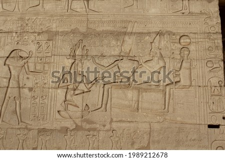 Man kneeling in front of the Theban triad in the mortuary temple of Ramesseum in Luxor in Egypt Stock photo ©