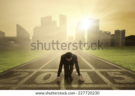 Man kneeling on track and ready to chase his dream in the future 2015