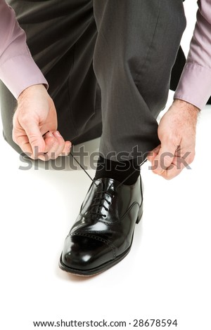 Man lacing up his shiny new black dress shoes.  Isolated on white. - stock photo