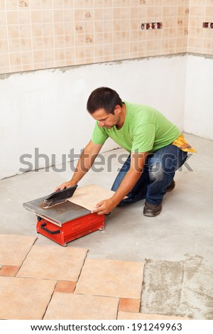 Man laying ceramic floor tiles on concrete - checking his work with a spirit level