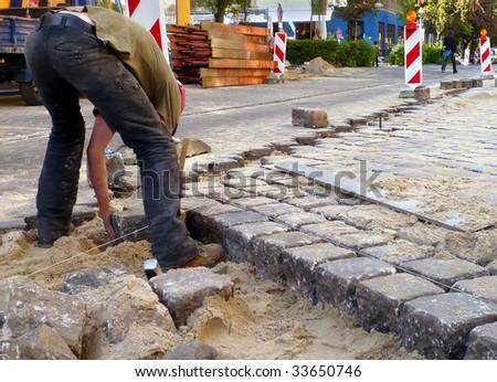 man laying cobblestone