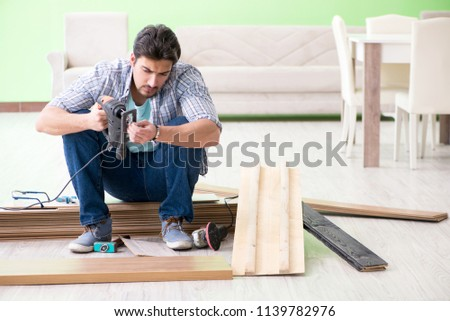 Man laying flooring at home #1139782976