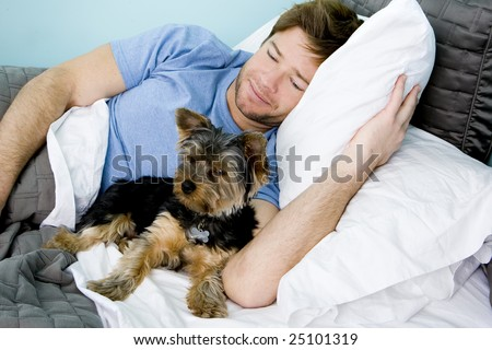Man laying in bed with a puppy