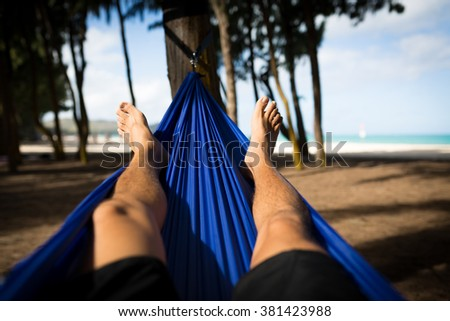 Man Laying in Hammock at Woodline on the Beach