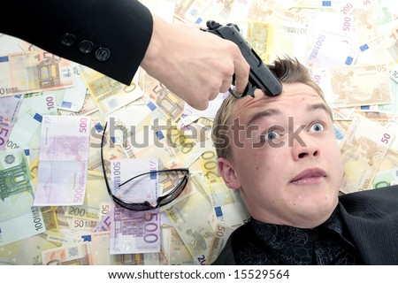 Man laying in money with gun pointed at head
