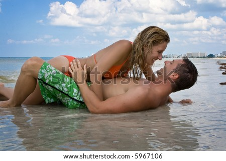 Man laying in the sand, woman laying on him, looking at each other