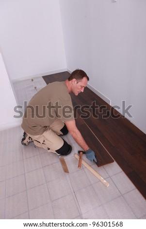 Man laying laminate flooring panels