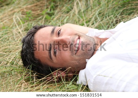 Man laying on his back in field