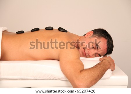 Man laying on massage bed with hot stones on his back - stock photo