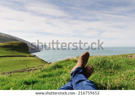 Man laying on the ground in a grass field, resting on a hill in the County Antrim, Northern Ireland