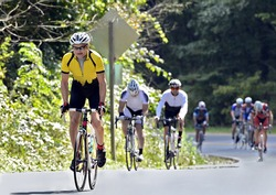 Man leading a group of riders up a mountain road during a race.