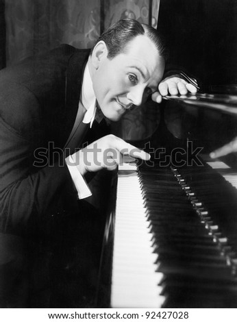 Man leaning over the piano playing the keys with one finger