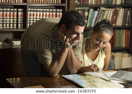 Man leans over table looking at woman studying map. He is resting his head on his hands. Horizontally framed photo.