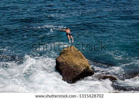 Man leaping from rock #1315628702