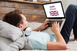 Man learning english on the internet with a laptop computer while lies down at home