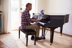 Man Learning To Play Piano Using Digital Tablet Application