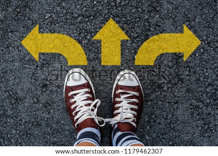 man legs in sneakers standing on road with three direction arrow choices, left, right or move forward #1179462307