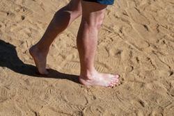 Man legs on sand. Male feet walking on beautiful sandy beach of hotel resort on Red sea in Egypt, doing and leave behind footprints in sand. Man on vacation in summertime. Travel and holiday concept.