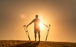 Man letting go of crutches able to walk again. Body recovery, healing, and miracle concept.