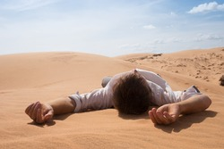 Man lie alone in the sunny desert. He is lost and out of breath. No water and energy. Concept for depression and noway situation in life