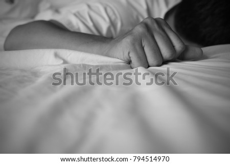 Man lies prone on the bed and tightly clutching bed sheet, feeling sad or depress, black and white tone, depressive disorder, depression psychotic concept