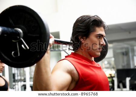 man lifting weights at the gym looking serious