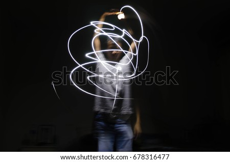 Man light painting curves in the dark