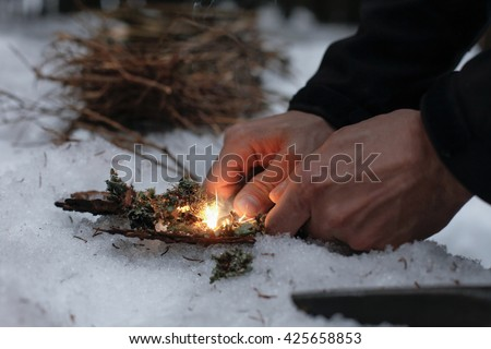 Stock Photo Man lighting a fire in a dark winter forest, preparing for an overnight sleep in nature, warming himself with DIY fire. Adventure, scouting, survival concept.