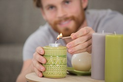 man lighting decorative candle in the home