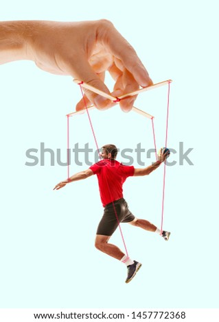 Man like a puppet in somebodies hands on blue background. Concept of unfair manipulation, phycology of exploitation, mental technique, motivation. Puppets and their masters. Possessive relationship. #1457772368