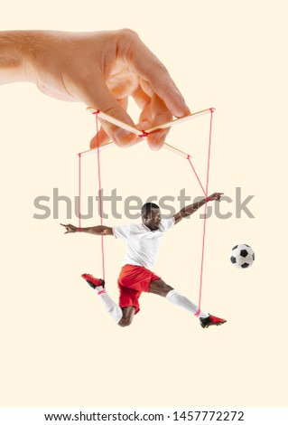 Man like a puppet in somebodies hands on yellow background. Concept of unfair manipulation, phycology of exploitation, mental technique, motivation. Puppets and their masters. Possessive relationship. #1457772272