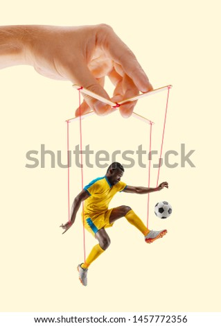 Man like a puppet in somebodies hands on yellow background. Concept of unfair manipulation, phycology of exploitation, mental technique, motivation. Puppets and their masters. Possessive relationship. #1457772356