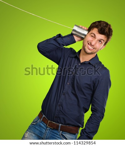 Man Listening From Tin Can Telephone against a green background