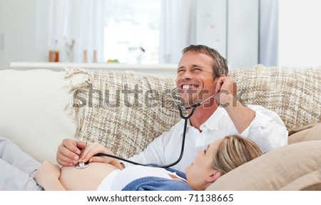 Man listening his wife's belly with his stethoscope at home