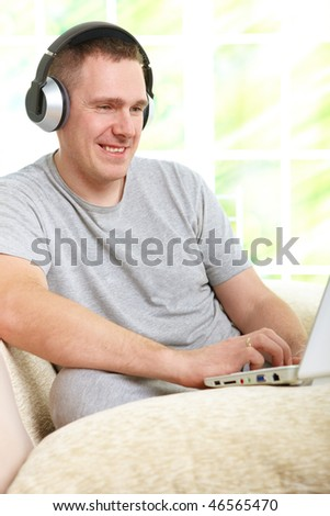 Man listening music with headphones and using laptop, sitting on sofa at home and smiling.