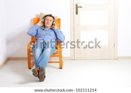 Man listening music with headphones sitting at home and smiling.