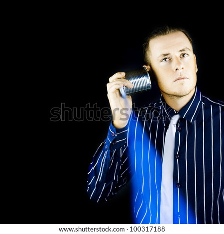 Man listening to a retro tin can phone which has been updated by technology to allow wireless communication and has planted the germ of an idea in his mind as he stares thoughtfully off into space