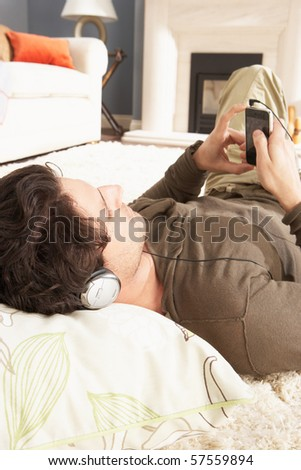 Man Listening To MP3 Player On Headphones Relaxing Laying On Rug At Home