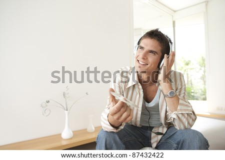 Man listening to music at home, using headphones
