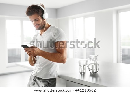 Man Listening To Music In Fashion Headphones Using Mobile Phone, Smartphone Indoors. Portrait Of Handsome Happy Relaxed Smiling Guy  Enjoying Music At Home. Entertainment, Communication Concept